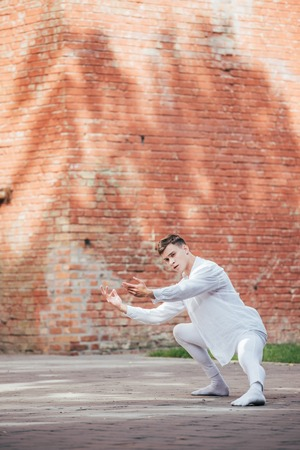 Handsome young male ballet dancer in white clothes dancing on urban street