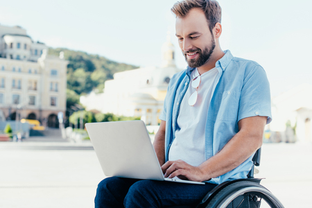 Cheerful handsome man in wheelchair using laptop on street