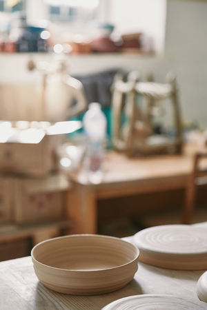 Selective focus of plates at table in pottery studio