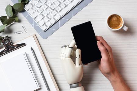 Partial view of businessman with cyborg hand using smartphone with blank screen at table with coffee cup in office Stock Photo