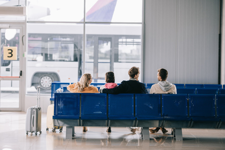 Rear view of young people sitting and waiting for flight in airport terminal