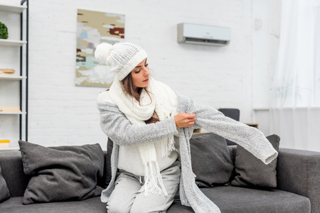 Freezed young woman putting on warm clothes while sitting on couch