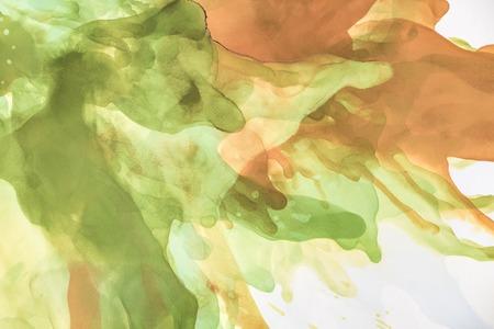 Mooie bruine en groene spatten van alcoholinkt als abstracte achtergrond
