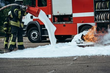 Częściowy widok strażaka gaszącego ogień pianą na ulicy Zdjęcie Seryjne