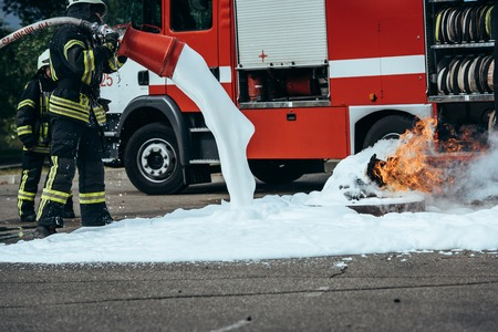 Partial view of firefighter extinguishing fire with foam on street 写真素材 - 111479355
