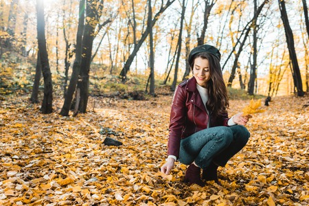 Beautiful young woman in stylish beret and leather jacket collecting yellow leaves in autumnal forest