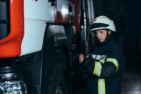 Female firefighter in helmet checking protective uniform at fire station