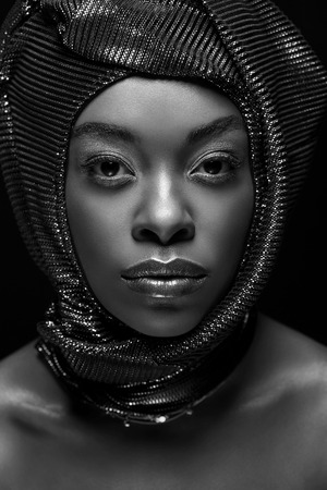 Black and white photo of stylish African American woman looking at camera isolated on black background