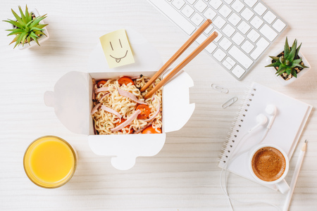Elevated view of wok box with chopsticks, orange juice, symbol of smile and coffee cup at table in office 写真素材