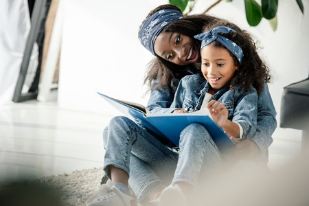 African American mother and smiling daughter looking at family photo album at home