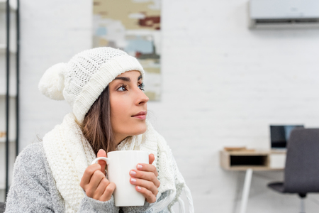 Thoughtful young woman in warm clothes holding cup of hot tea at home and looking away Standard-Bild