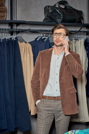 Handsome man talking by smartphone while shopping in boutique Foto de archivo - 111483416