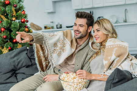 Happy young couple with popcorn watching movie at home Stock Photo