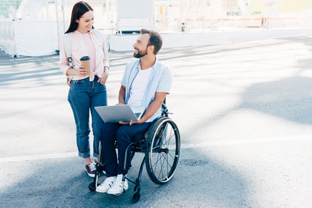 Handsome boyfriend in wheelchair using laptop and girlfriend standing with coffee in paper cup on street, looking at each other
