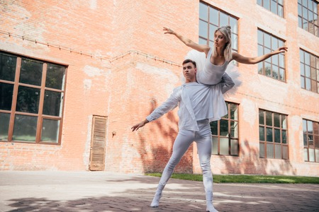 Low angle view of young ballet dancers in white clothes dancing on urban city street Foto de archivo - 111483485