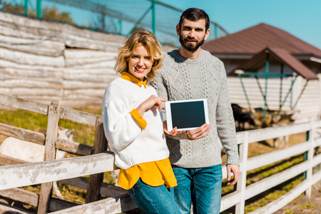 Adult couple of farmers showing digital tablet with blank screen near wooden fence at farm Stock Photo - 111483490