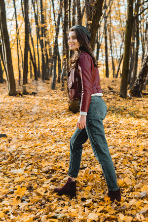 Attractive stylish woman in beret and leather jacket walking in autumnal park