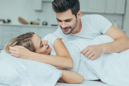 Beautiful young couple cuddling in bed at home Stock fotó