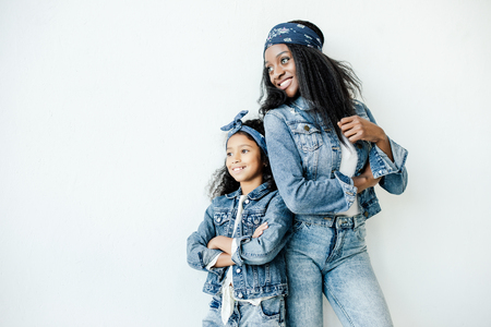 Stylish African American mother and daughter in similar clothing posing at wall at home Reklamní fotografie