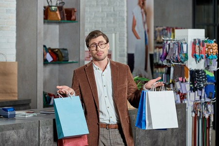Young man in eyeglasses holding shopping bags and looking at camera in store Foto de archivo - 111483504
