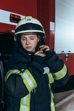 Portrait of female firefighter in uniform checking helmet at fire department