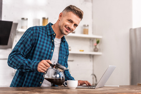 Handsome smiling man pouring coffee and using laptop at home