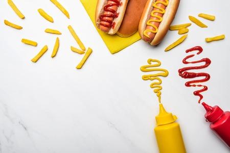 Vue de dessus des hot-dogs avec de la moutarde et du ketchup sur une surface en marbre blanc Banque d'images