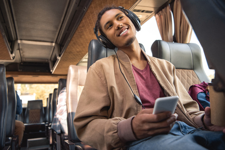 Cheerful mixed race man in headphones sitting with paper coffee cup and smartphone in travel bus