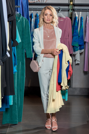 Attractive young woman holding fashionable clothes and looking at camera while shopping in boutique Foto de archivo - 111483608
