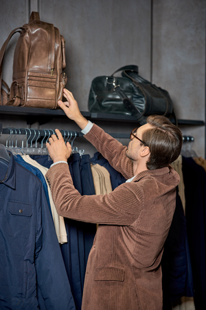 Young man in eyeglasses holding backpack while shopping in boutique Foto de archivo - 111483610