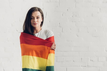 Young transgender man covering with pride flag and looking at camera in front of white brick wall background