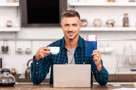 Happy man holding cup of coffee and passport with ticket while using laptop at home