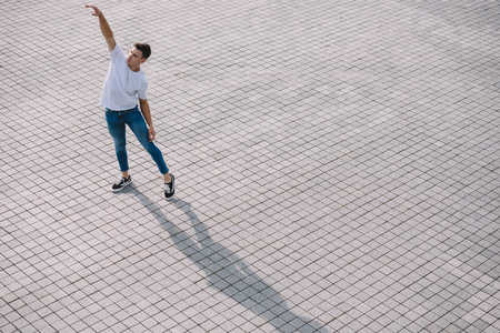 High angle view of young man performing contemporary dance on street