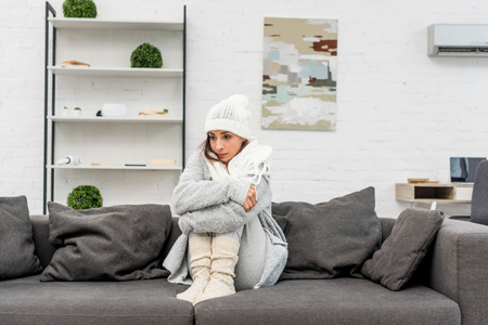 Freezed young woman in warm clothes sitting on couch at home and looking away