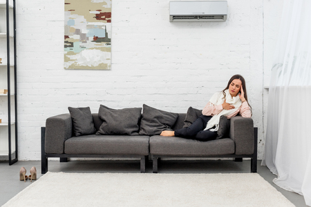 Ill young woman lying on couch under air condition at home Stock Photo