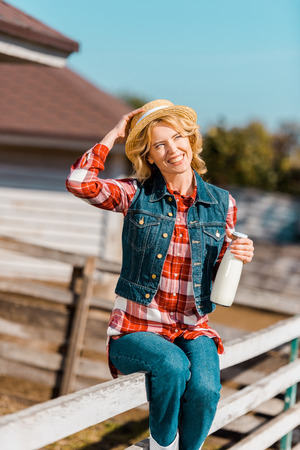Happy female farmer holding bottle of milk and sitting on wooden fence at ranch