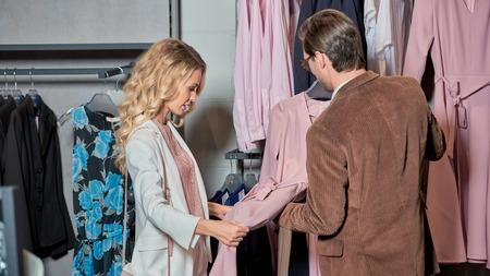 Stylish couple choosing fashionable clothes in boutique Foto de archivo - 111483872