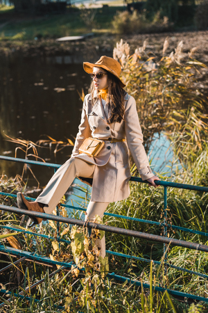 Fashionable woman in sunglasses, trench coat and hat sitting on railing near pond