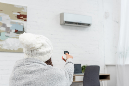 Rear view of freezed young woman in sweater pointing at air conditioner with remote control Фото со стока