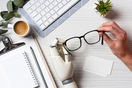 Cropped image of businessman with cyborg hand holding eyeglasses at table with empty visit cards and computer keyboard in office