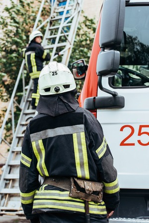 Back view of firefighter in protective uniform and helmet looking at colleague on ladder on street Stock Photo