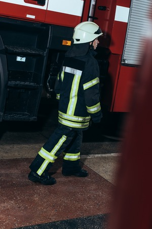 Female firefighter in uniform and helmet walking at fire station Stock Photo