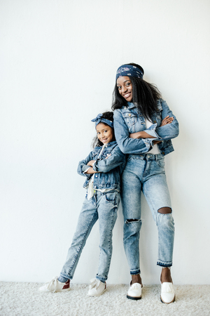 Smiling African American mother and daughter in similar clothing posing at wall at home 版權商用圖片