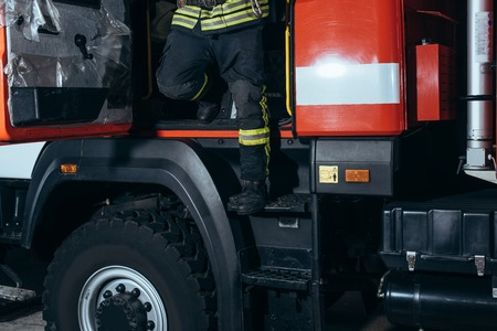Partial view of firefighter in fireproof uniform getting out of truck at fire station Stock Photo