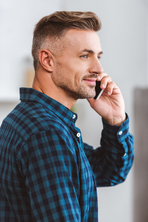 Side view of handsome smiling man talking by smartphone and looking away at home 版權商用圖片 - 111485760