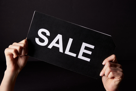 Cropped shot of woman holding banner with sale sign isolated on black, black Friday concept Stockfoto