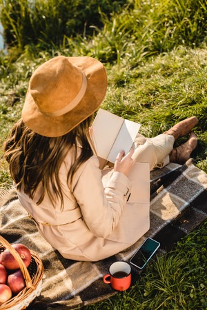 Rear view of stylish elegant woman in hat reading book on blanket near pond outdoors