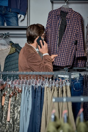Man talking by smartphone and choosing fashionable clothes in shop Foto de archivo - 111533872