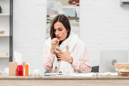 Zieke jonge zakenvrouw die hoest op de werkplek Stockfoto