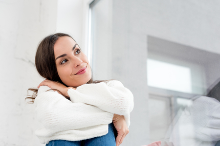 Bottom view of smiling thoughtful young woman looking up Stock Photo